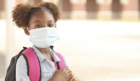 a girl waiting for a school bus in a protective mask