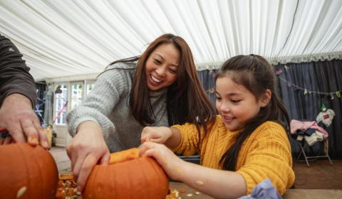 mother and daughter carving a pumpkin