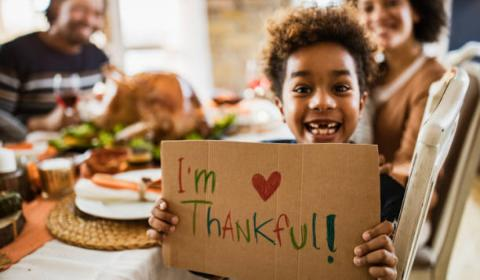"""a child holding up a sign that says """"i love thanksgiving"""""""